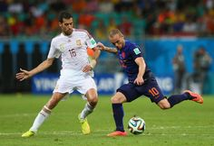 Sergio Busquets of Spain challenges Wesley Sneijder of the Netherlands during the 2014 FIFA World Cup Brazil Group B match between Spain and Netherlands at Arena Fonte Nova on June 13, 2014 in Salvador, Brazil.