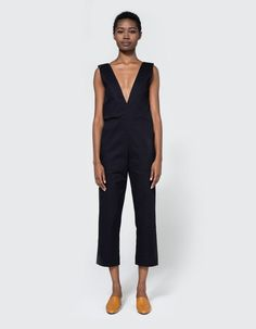Tailored jumpsuit from Toit Volant in Navy. Thick tank straps. Narrow deep V-neckline. Concealed back zip closure. Slanted front patch pockets. Back patch pockets. Slim, straight leg. Cropped length. Unlined. • Fine-line stretch twill • 65% poly 35% c