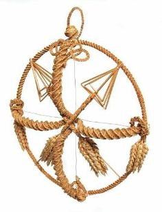 This corn dolly, called the 'Ambridge Circle', was devised and made by Alec Coker after appearing as a corn dolly lecturer on BBC Radio 4's serial 'The Archers' in 1972. It consists of a spirally woven circle inside which is a spirally woven cross. In the upper half are two plaited and arrows, and in the bottom half are two bunches of corn ears. (MERL/86/124/1)