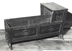 A baby's cradle, probably about 1680.  Date Made:  about 1918 to 1923  Description  A baby's cradle, probably about 1680; the moulded rectangular top now split and hinged; the panelled superstructure at the head end carved and initialled BK and HB; the panelled body carved with rosettes and diamonds and raised on shaped rockers; English, South Yorkshire; considerable restoration including rear plank of top, sections of panels, later carving; new base-boards; head rocker replaced; generally…