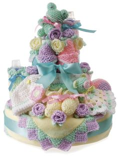 Create a beautiful baby gift that doubles as the centerpiece for a baby shower.    Soft and cuddly crocheted baby blanket, toys, bib, edgings, bottle cover and more are combined with purchased cloth and disposable diapers to create a gorgeous tiered cake that will be the highlight of a shower.