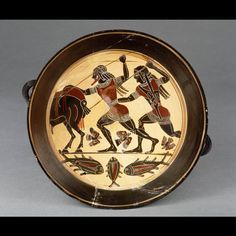 KASTOR AND POLYDEUKES  The brothers of Helen (probably) attack the Kalydonian Boar. The fish beneath the ground-line indicates a lake or stream. Spartan black-figure wine-cup, c. 555 bc.