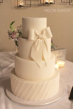Classic White on White wedding cake with traditional swiss dots, pleating and silk inspired fondant bow.  #MidoriBakery