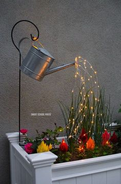 Glowing Watering Can with Fairy Lights - How neat is this? It's SO EASY to make! Hanging watering can with lights that look like it is pouring water. #gardendesign