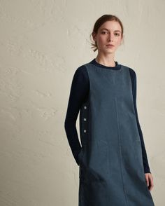 Workwear dress in washed, garment-dyed cotton. Boat-ish neck. Corozo shank buttons at either side. Two large stitched-through pockets. Single patch pocket at back. Twin needle topstitching.