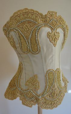 New Gold Dream Corset  Biscuit coloured satin with heavy gold appliqué, hand beaded with Swarovski Crystals. Silk lined. Closed front corset with modesty panel and satin ribbon laced eyelets at the back. This is constructed using up-cycled fabrics and embellishment. Client consultation would approve alternative satin colour and detailing before construction begins.  As there is no front opening, this corset slips over the head with the ribbon fully loosened and is then tightened from the…