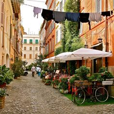 beautiful street for pedestrians, bicycles, scooters and diners in rome.