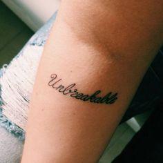 Forearm tattoo saying Unbreakable on Anastasia.