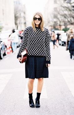 A black and white sweater is worn with a brocade knee-length skirt, socks, and peep-toe heels