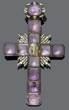AMETHYST AND SILVER PENDANT, probably Russia, 19th century. Large cross pendant, set with 10 octagonal amethysts, table cut. In the centre, an oval miniature painting on porcelain with a crucifixion scene, chipped. Ray-like decoration in between the beams, completely set with numerous faceted glass stones. Eyelet decorated with 1 amethyst and glass stones, probably slightly later. From the heirs of Baron Anton Kiss (1880-1970), son of Katharina Schratt, Schloss Mondsee.