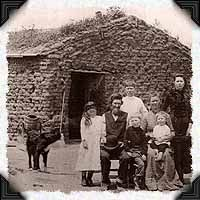 "1880s Nebraska: It wasn't at all unusual for a sod house to have walls three feet thick. When rain began to deteriorate the exterior face, a soddie dweller simply laid another layer of ""Nebraska brick"" on it. In addition to a sturdy house, this 1880's Custer County family apparently has a very good well which can be seen in the larger view."""