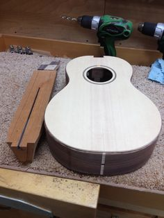 Clean up body, rout dovetail, drill tuner holes, glue fretboard onto neck, rout binding channels, glue in top binding