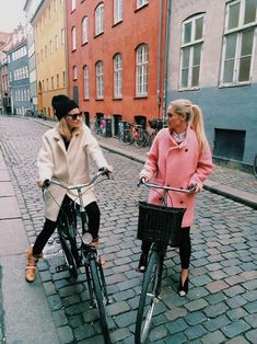 Two girls chat as they pose with their bicycles on a brick street in Europe - https://www.facebook.com/GreatMountainBiking/