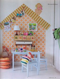 wallpaper placed in shape of a house as a backdrop for a shelf and child's art hanging