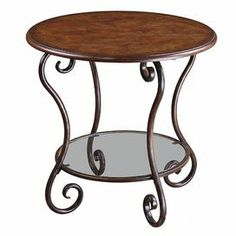"""End table with a scrolling forged metal base and glass bottom display shelf.   Product: End tableConstruction Material: MDF, glass, poplar burl and metalColor: Chestnut brown and clearFeatures:  Distressed, hand forged metal base in deep wood tonesClear bottom shelf Dimensions: 24"""" H x 25"""" Diameter"""