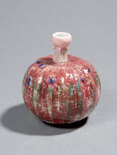 """Doat Taxile (1851-1938) """" Coloquinte """" Vase de forme naturaliste en porcelaine, à panse cotelée et nervurée émaillée rose lie-de-vin nuancé de blanc-vert. Les boursouflures du cucurbitacé sont émaillées bleu. La tige est émaillée blanc et rose. Signée, située """"Sèvres"""" et datée """"1920""""."""