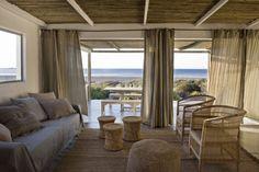 salon cosy avec meubles en osier et en rotin rideaux en lin et cajnapé recouvert de tissu