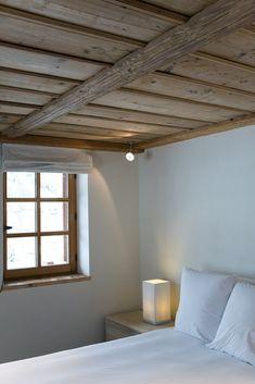 Empty room with wood ceiling, white bedding + simple lamp on the night stand