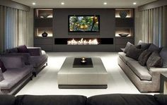 grey and white basement with a modern gas fireplace and wall mounted TV in spacious entertainment area