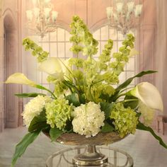 White Calla Lilly and Bells of Ireland Silk Floral Centerpiece in Silver Bowl - Clean, crisp white silk calla lilies, Bells of Ireland, white and green silk hydrangeas arranged in a hammered, silver-toned metal pedestal vase. Our silk design provide