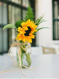 Sunflowers in jam jars as decorations for a yellow wedding theme. How easy would these be to DIY?