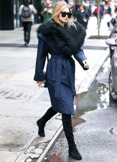Gigi Hadid wears a navy topper with an oversized fur collar, black sunglasses and black over-the-knee boots.