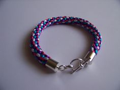 This Kumihimo Bracelet is made using 2mm Rattail in Pink, White, Turquoise and Deep Purple.