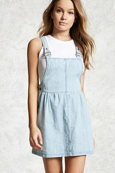 A sleeveless overall dress crafted from woven denim with adjustable straps, a square neckline, a square-cut back, a mini length, and buttoned sides.