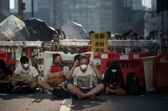 Umbrella Revolution Hong Kong, Pro-democracy protesters sit in front of a barricade in the Admiralty district of Hong Kong on October 13, 2014. Hong Kong police started removing street barricades at sites where pro-democracy demonstrators have been holding more than two weeks of rallies, paralysing parts of the Chinese financial hub. AFP PHOTO / Ed JONES (Photo credit should read ED JONES/AFP/Getty Images)