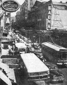 La concurrida calle de 16 de Septiembre, vista desde la esquina con San Juan de Letrán, hoy el Eje Central, a finales de los años cuarenta. Entre los edificios del lado derecho destaca el cine Olimpia, abierto en 1921, cuya estructura aún existe y en la actualidad alberga a la Capital del Sexo. Hay que apreciar los vehículos de la época.