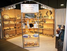 Pottery booth with lots of display space and great lighting - Photo links to page with helpful and detailed instructions about how the artists created their booth.