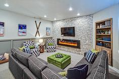This basement space from Kristen Thomas was designed to incorporate team colors of the Seattle Seahawks. It features rustic stone walls with floating shelves of unfinished wood alongside modern elements such as an inset fireplace. Also featured are a dedicated home theater and a refined bathroom.