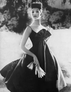 1959 Simone in steel gray poult-de-soie dinner dress, the deep décolletage is masked by a fanned bow, the skirt swings free from the waist, by Sophie of Saks Fifth Avenue