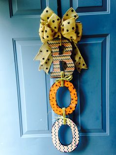 My version of the BOO Doorhang.  Fun project for the weekend!    Wood Letters, painted black;Halloween Papers (Hobby Lobby); Burlap Bow, embellished with acrylic paint (I want to add orange dots, too!); Modge Podge; Rafia