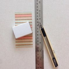 Using the matchbox as a gauge, measure and trim the piece of pattern paper out by wrapping around the matchbox cover...