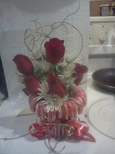 Candy Canes glued to an old coffee can.. filled with flowers and wrapped in a red bow :)