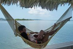 Honeymooners in a palapa hammock - Roatan, Barefoot Cay Resort