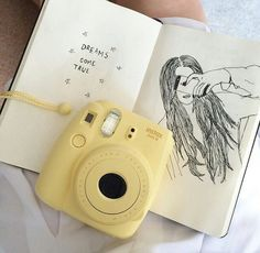 Yellow Instax Mini 8 with sketchbook on lap
