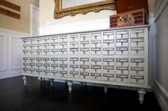 Buffet made from card catalog cabinets.  Looks almost old world with the gray-blue paint and aged gold/bronze and cream fixtures