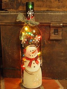 This is a recycled wine bottle that I have handpainted with a snowman. It has been sealed and sprinkled with german glass glitter and tied with a homespun bow.