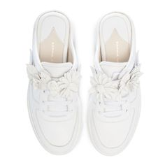 Stand out in our white mule sneaker with flower embellished velcro strap.