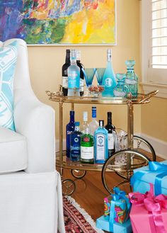 Bar cart stocked with aqua libations. From beautiful home of Beverly Wells, who worked with her daughter, designer Tobi Fairley.