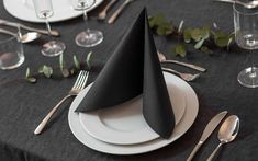 black folded napkin, on white plates, silverware arranged around them, napkin folding with rings