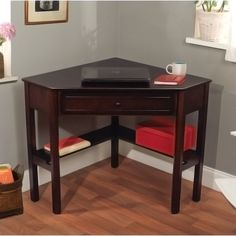 Add functional style to your living area with this corner writing desk. It is made of manufactured wood for ultimate durability. A shelf under the writing surface provides a perfect place for books, and the drawer can house writing instruments.