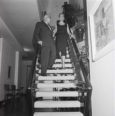 Joan Crawford and her fourth and final husband, Pepsi-Cola CEO Alfred N. Steele, descend the staircase of their 18-room New York City duplex penthouse