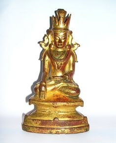 Gilded and lacquered bronze sculpture of the seated and crowned Buddha.  He is depicted with his left hand in his lap and his right hand in bhumisparsamudra, suggesting the moment of the Enlightenment.  He is seated on a waisted triangular throne on which lightly engraved lotus petals can be seen.  The once elaborate crown is now broken.  It is missing the top most finial and some of the triangular elements of the crown are broken; the side flanges typical of post-Pagan scultpure are also…