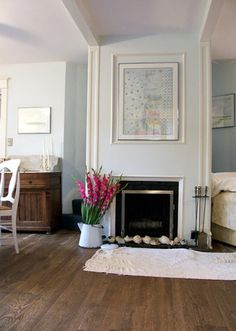 The palest blue walls with bright white trim and wood floors. Also, metal bucket vase yum #fireplace #blue #livingroom