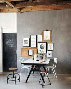 Industrial living room / dining room with picture frames, wooden stools, white chairs, a folding table and botanic plants