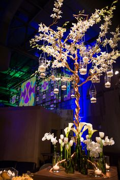 Our floral trees are adorned with antique bottles and filled with white flowers.  #mccallssf #mccallscatering #mccallsfloral #exploratorium #eventdecor