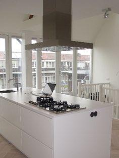 De witte kleur van de keuken verruimt het beeld verder